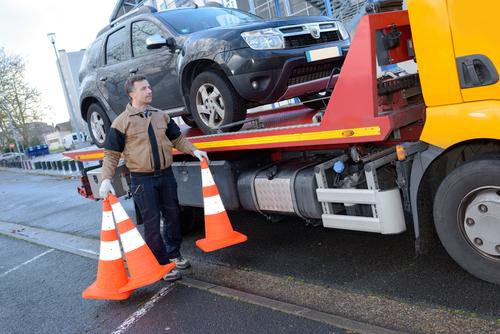 a tow truck takes away a broken car
