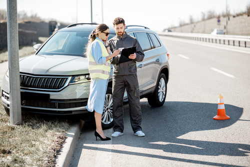 Woman with road assistance worker signing some documents standing near the car in road accident on the highway