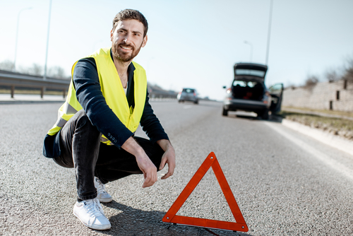 Portrait of a man near the emergency sign on the roadside with broken car on the background
